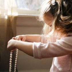 Little girl plays with pearl necklace