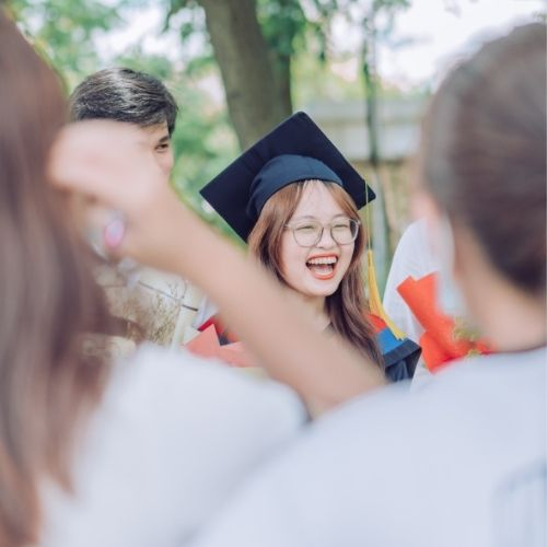 A woman smiles broadly on her graduation day as her friends look on
