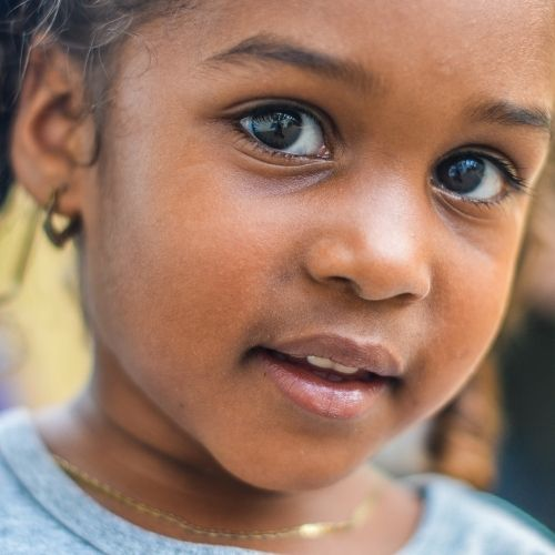 Little girl poses for the camera and shows her jewellery