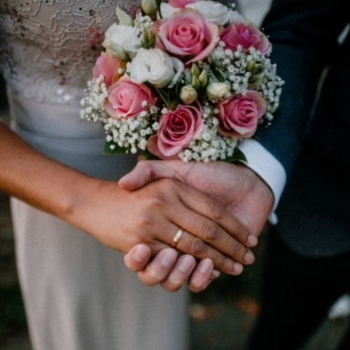 A bride and groom hold hands while the bride shows her bouquet in a close up