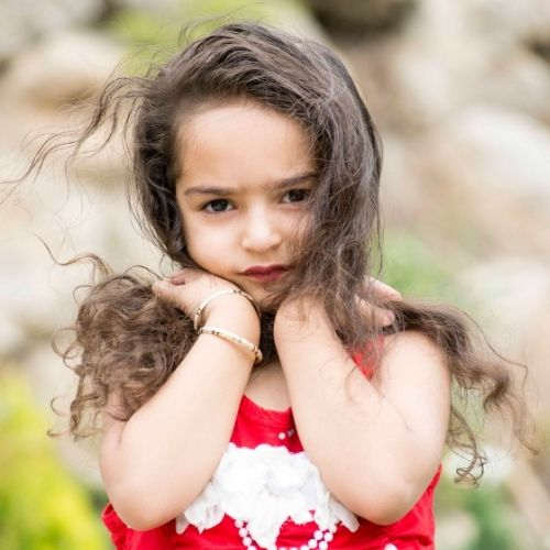 Little girl poses with her hands on her shoulders.