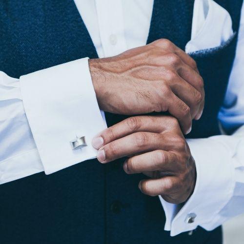 A groom adjusts his cufflinks
