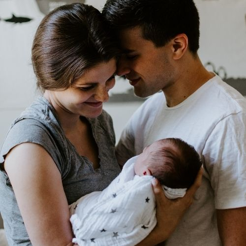 New parents hold their newborn baby